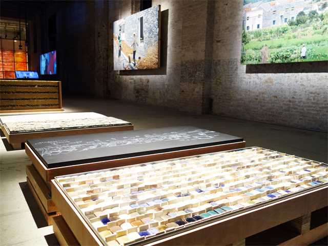 A series of pallets containing tiles, crushed rubble and rammed earth show the handmade materials …